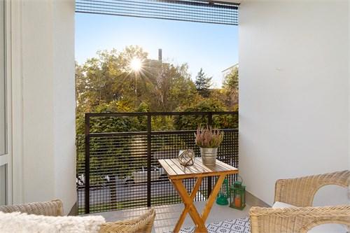 Solig balkong med grönskande utsikt